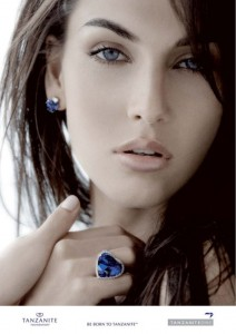 A model wearing a heart shaped cut natural tanzanite gemstone set in a ring and a similar gemstone set in the earring. A press release photo from the TanzaniteOne Mining Group.
