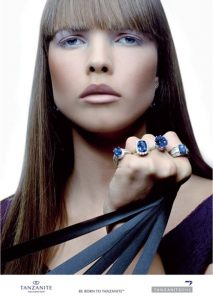 A press release photo from the TanzaniteOne Mining Group. A model wearing tanzanite gemstones of various cuts such as oval and cushion cut