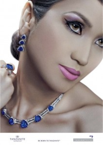 A model wearing a necklace set with numerous trillion cut natural tanzanite gemstones, a large emerald cut tanzanite gemtone set in a ring and three trillion cut gemstones set in the earring