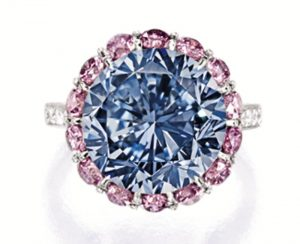 Premier Blue diamond set as the centerpiece of a platinum ring surrounded by pink diamonds