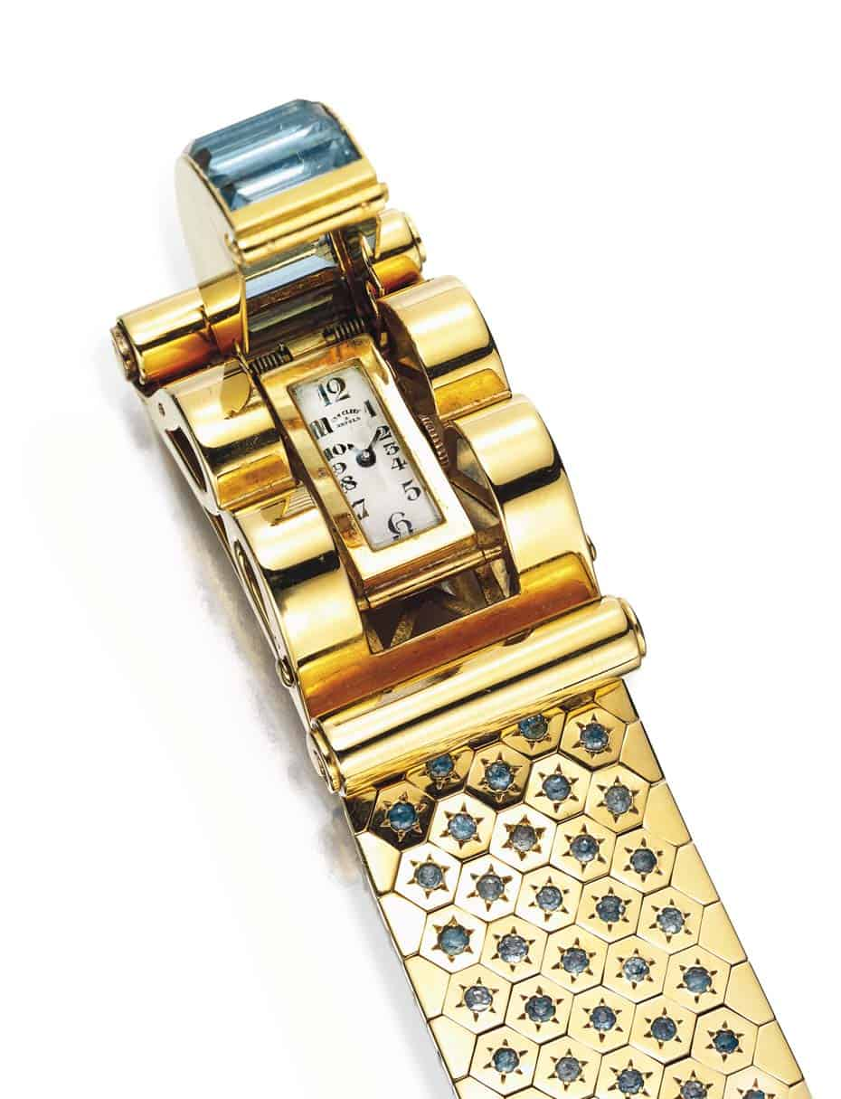 Lot 124 - Rectangular-cut  aquamarine and gold buckle clasp opening to reveal a watch dial