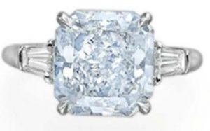 Lot 74 - A Colored Diamond And Diamond Ring  set with a 5.70-carat, cut-cornered rectanguar-cut, VS1-clarity, fancy-blue diamond