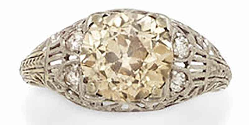 Lot 425 - A COLORED DIAMOND, DIAMOND AND PLATINUM RING