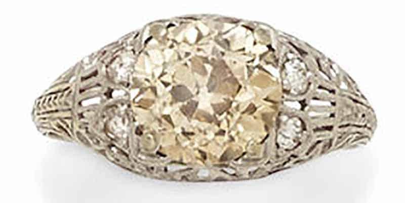 Lot 425 - A COLORED DIAMOND, DIAMOND AND PLATINUM RING