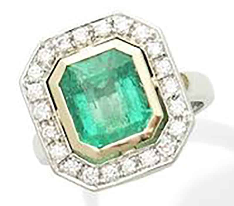 LOT 248 - AN EMERALD AND DIAMOND CLUSTER RING